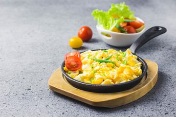Soft creamy scrambled eggs in cast iron skillet and cherry tomatoes. Selective focus, space for text.