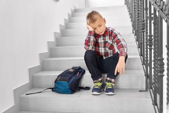 Sad blond boy sitting on stairs in corridor of school.