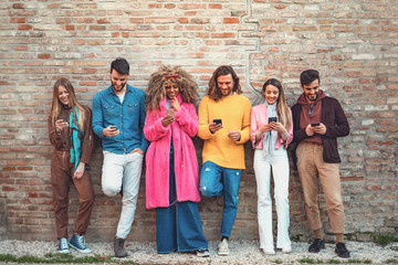 Multiracial friends using smartphone against an ancient wall - Young people addicted by mobile smart phone - Technology concept with always connected . using social media. Filtered image Wall mural