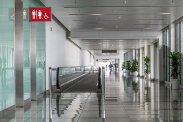 Empty hallway in airport hall with mobile walkway and toilet entrances.