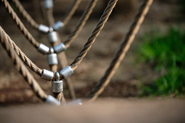Abstract picture shot on a playground at a climbing fram with a detail with bright beige ropes connected via metal. Seen in Nuremberg, Germany, June 2019