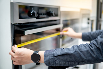 Male interior designer hand using tape measure on oven in the kitchen showroom in furniture store. Handy cooking appliance on domestic kitchen counter. Home improvement concept