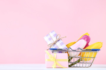 Small shopping cart with tulips and gift boxes on pink background