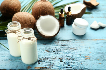 Wall Mural - Coconut milk in bottles with fruit and palm leafs on blue wooden table