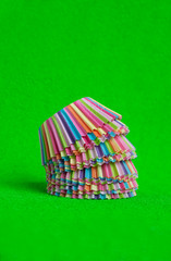 Rainbow colored paper baking cups for muffins and cupcakes on a green background minimal creative concept. Space for copy.