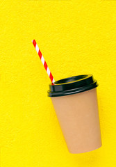Paper Coffee cup to take away on yellow background. Top view.