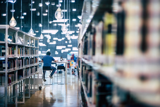 People studying in public modern library - man sitting viewed from back working at computer laptop - city space for students to learn and teach - defocused book - focus on male in background