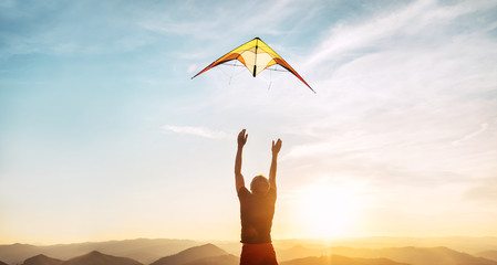Man starting to fly bright kite in sunset sky over the high mountain. Successful startup concept image.