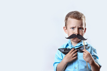 frowning serious boy in a light shirt put a mustache on a stick and a bow tie on his face to make him look older.