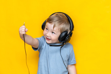 A smiling boy unplug his headphone and show plug to camera on isolated yellow background