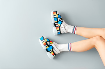 Beautiful female legs in white trendy socks posing in colorful fashionable high wedge leather sandals on gray background. Asian anime style concept. Womens legs wearing high sole summer stylish shoes.