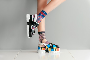 Beautiful female legs in mismatched trendy socks standing in two different fashionable high wedge leather sandals on white surface. Odd disargonized  young girl wearing high sole summer stylish shoes.