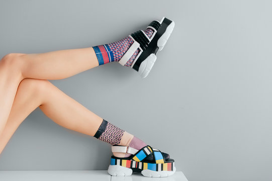 Beautiful female legs in mismatched trendy socks posing in two different fashionable high wedge leather sandals on gray background. Odd disargonized  young girl wearing high sole summer stylish shoes.