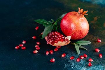 Red juice pomegranate on dark background. Ripe pomegranate with leaves on a dark background