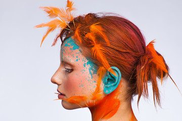 Portrait of a beautiful model with creative make-up and hairstyle using orange feathers