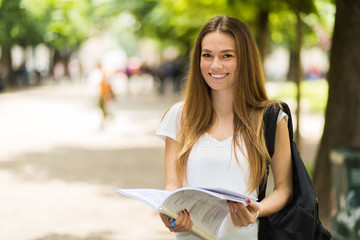 Female student holding a book outdoor in the park and smiling
