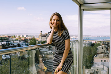 portrait of young blonde haired woman, smiling, wearing striped dress standing and leaning on the terrace, balcony, old city beneath, overcast sky