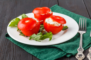 tomatoes stuffed with spinach, cheese and herbs, close up. Delicious and nutritious vegetarian meal