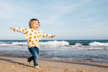 Happy little girl running barefoot on the beach Wall mural