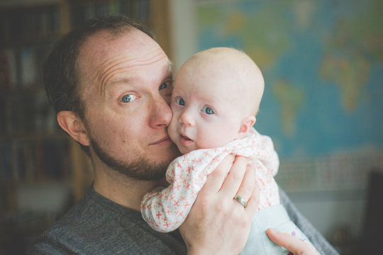 Portrait of father holding his baby daughter