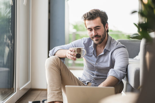 Young man sitting at home on floor, using laptop, drinking coffee