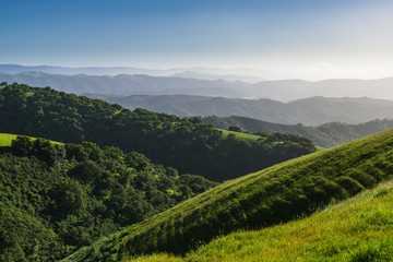 Landscape scene of lush green hills, meadows, oak forest, and multiple mountain ridges fading into the distance - Toro Park near Monterey, California
