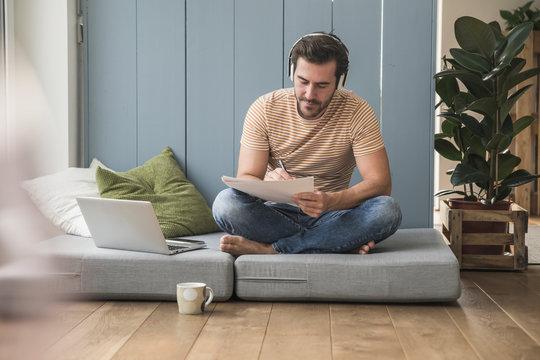 Young man sitting on mattress, taking notes, using headphones