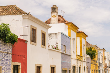 Old, colorful buildings with ornate trim and tiles line a street in Tavira, Portugal