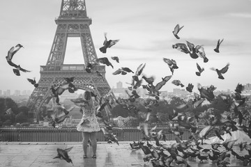 soft focus on tourist taking picture on eiffel tower with pigeons flying around