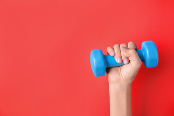 Woman holding vinyl dumbbell on color background, closeup with space for text Fototapete