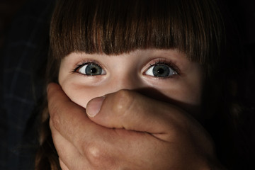 Adult man covering scared little girl's mouth, closeup. Child in danger