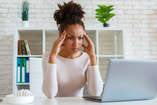 Woman have a chronic headache, touching temples to relieve pain during working on laptop