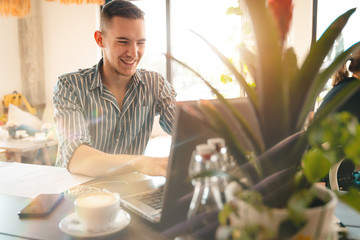 Handsome man using laptop while sitting indoors. Freelance work. place of work. New business. - Stock Image