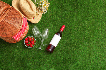 Flat lay composition with picnic basket, wine and strawberries on grass, space for text
