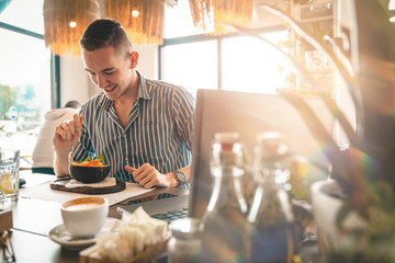 Handsome man eating a salad while doing business. - Stock Image