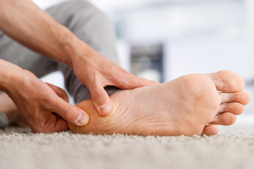 Man hands giving foot massage to yourself after a long walk, suffering from pain in heel spur, close up, indoors. Flat feet, leg fatigue, plantar fasciitis