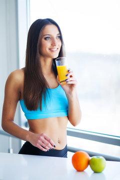 Beautiful smiling woman enjoying a glass of orange juice in the morning