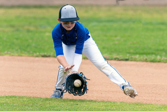 Youth baseball player in blue uniform fielding a ground ball into his glove in the infield during a game.