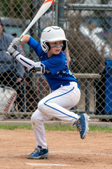 Youth baseball player in blue uniform and white helmet lifts leg in preparation to hit and swing the bat.