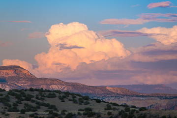 Sunset paints cumulus clouds and thunderheads in soft colors of pink, purple and peach over the colorful desert landscape of Ghost Ranch, Abiquiu, New Mexico