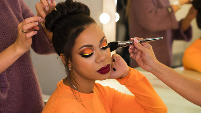 Hairstylist and make-up artist makeup and updo for stylish young African-American woman in beauty parlor. Rich colors. Party image. Beauty industry