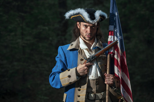 Man dressed as soldier of War of Independence United States aims from pistol with flag.  4 july independence day of USA concept photo composition: soldier and flag.