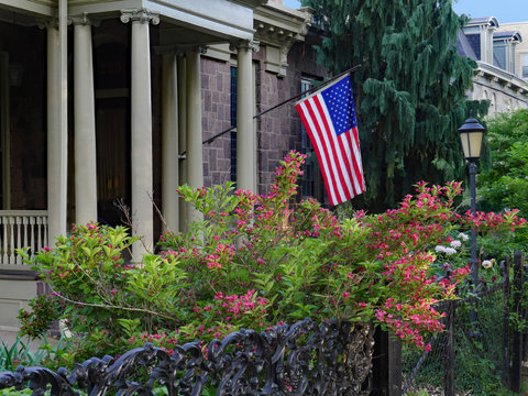 front garden with flowering bush and American flag