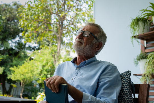 senior man happiness sitting and reading book at balcony near garden at nursing home for relaxing