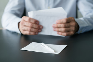 Business correspondence. Cropped shot of man sitting at desk with stack of white envelopes and blank sheet of paper. Copy space.
