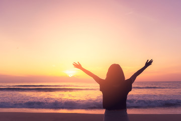Copy space of woman rise hand up on sunset sky at beach and island background.