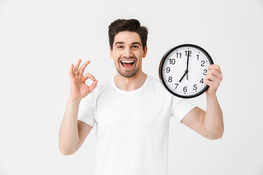 Shocked excited happy young man posing isolated over white wall background holding clock.