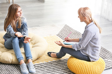 Female psychologist working with teenage girl in office Wall mural