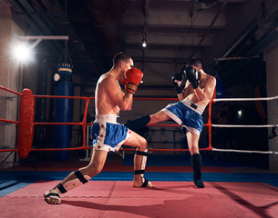 Two professional sportsmen boxers exercising kickboxing in the ring at the sport club