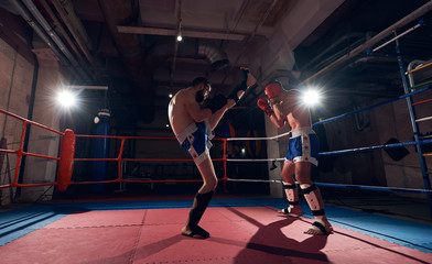 Two anger kickboxers training kickboxing in the ring at the health club
